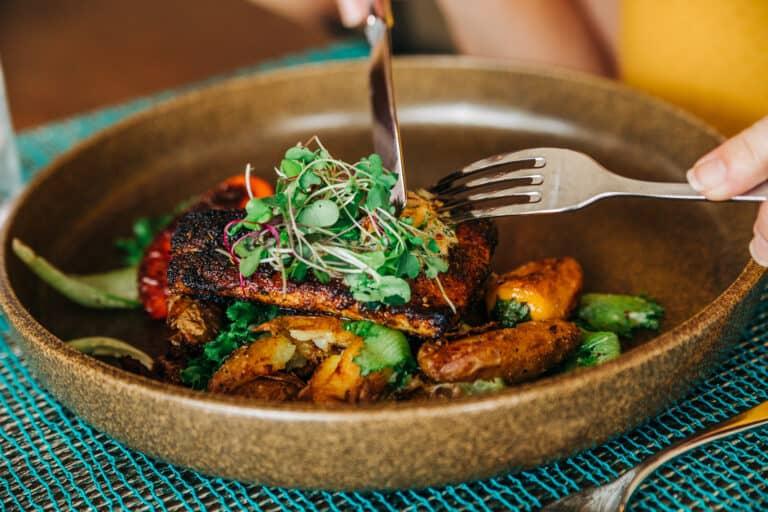 Fork and knife cutting into shrimp salad