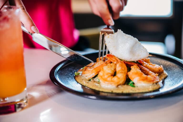 Fork and knife cutting into shrimp dish
