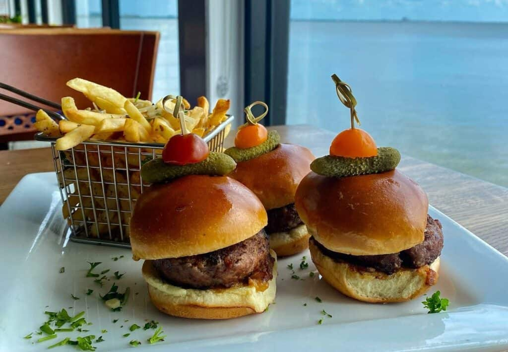 4 slider burgers on a plate with truffle fries