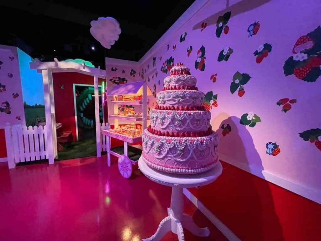 a 5-tier pink cake in an all pink rom with strawberry stickers on the wall