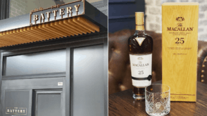 """exterior of a restaurant with a sign reading """"The Battery"""" next to a tall glass bottle of bourbon and an upright yellow menu"""