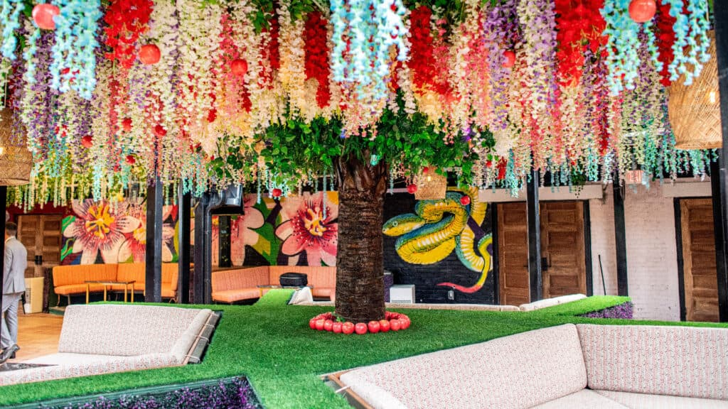 a large well lit room with flower arrangements hanging from the wall and a tree at the center