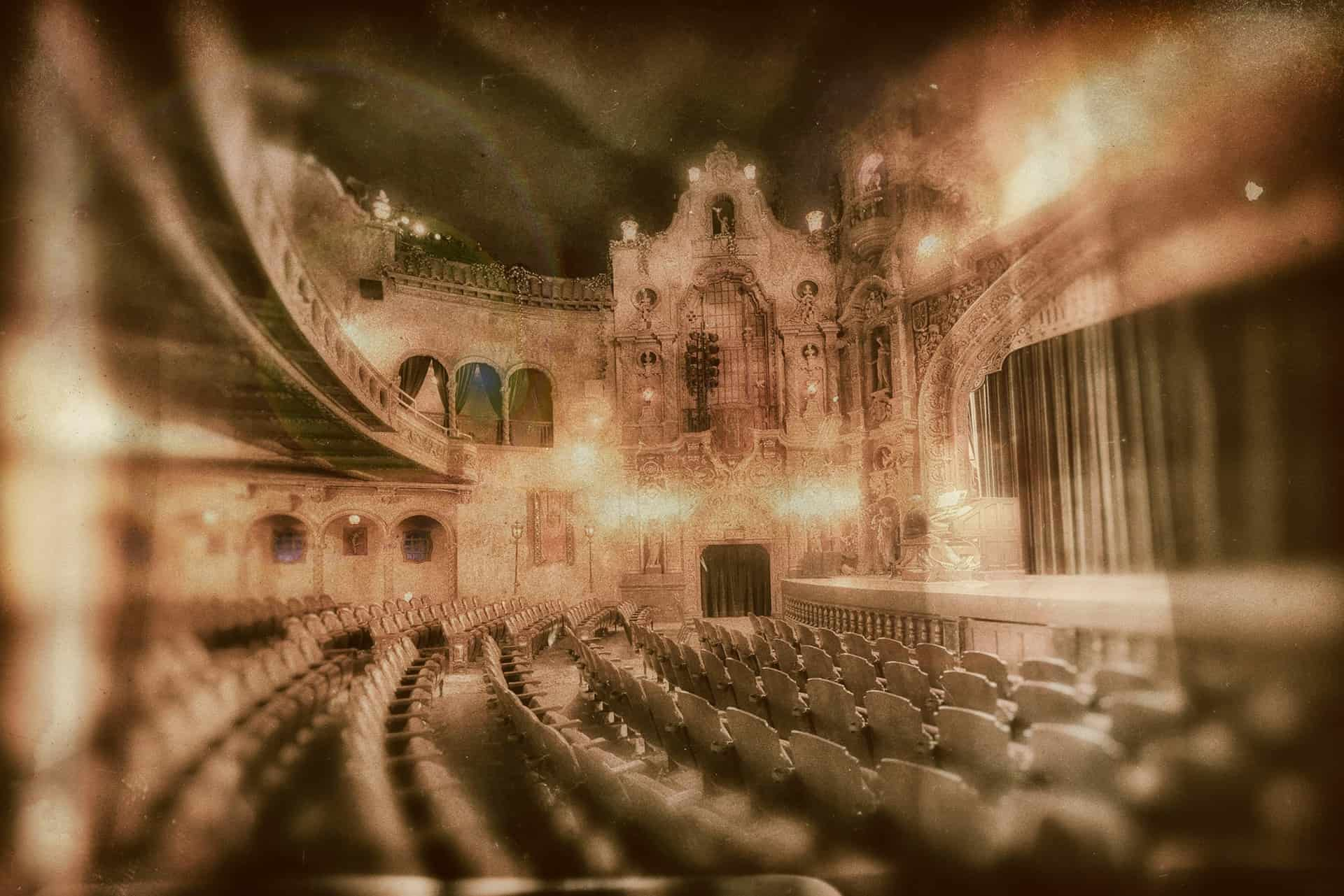 inside a large theatre with lights and a velvet curtain