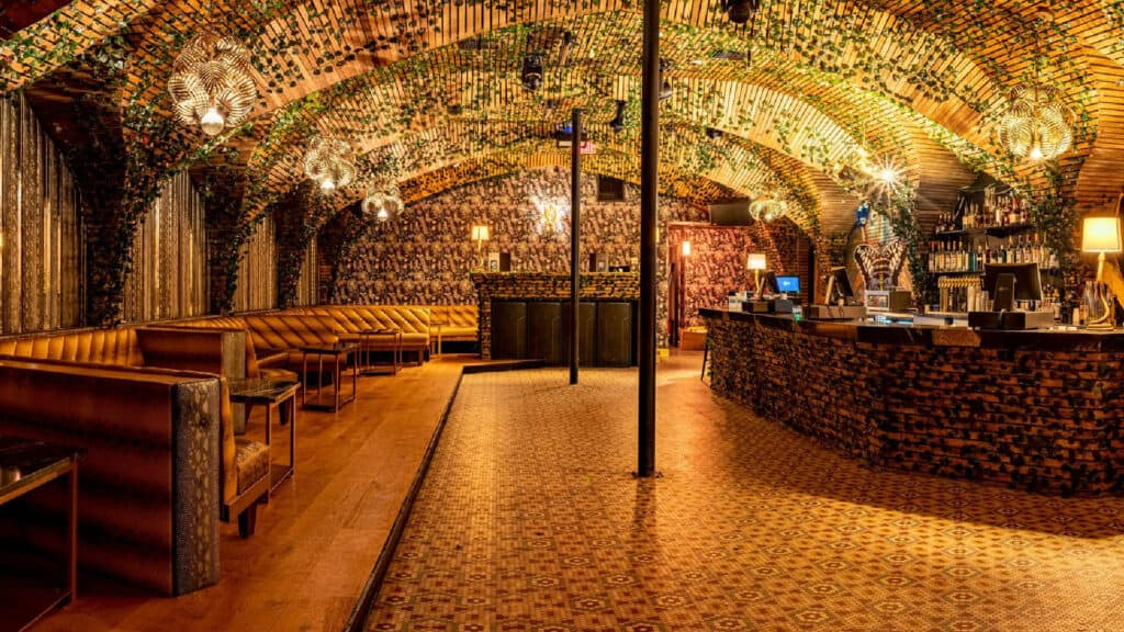 inside a giant gold room with a wrap around bar and leather booth seating