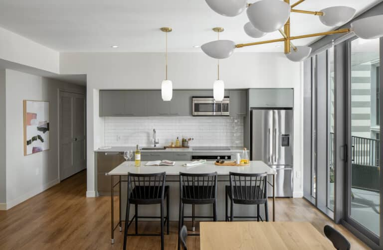 inside a large apartment with bay windows and granite countertops