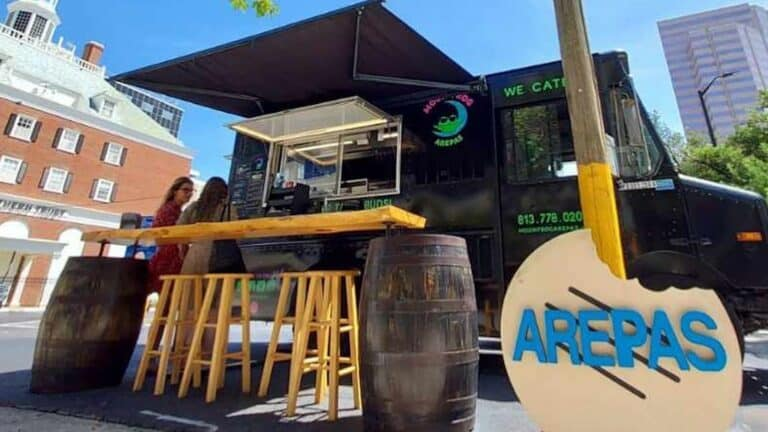 exterior of a food truck with a black wrap and a wooden high top table set on the sidewalk