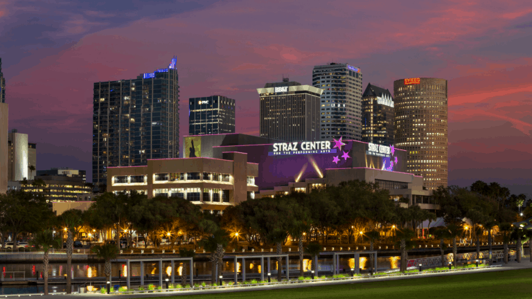 a large theater with purple lights cast on it on the waterfront